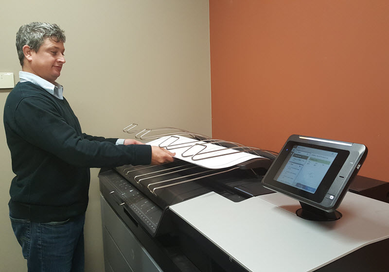 man pulling paper from a printer
