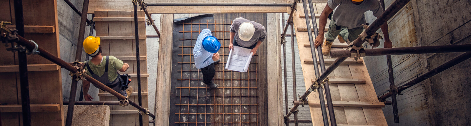 bird's eye view of men looking at plans on construction site